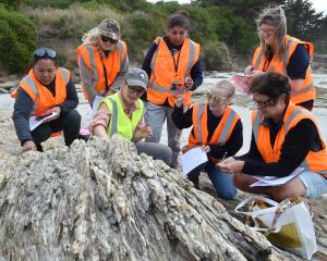 University of Otago geology department teaching fellow Dr Sophie Briggs (centre left) explains...