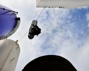Dunedin senior firefighter Joe Begley is lowered from a silo at the former Cadbury premises...