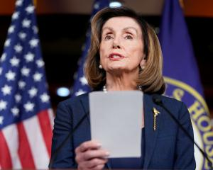 US Speaker of the House Nancy Pelosi holds and discusses a report saying that President Donald...