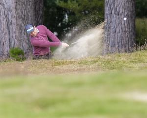 Nic Kay hits the ball out of the bunker on the third hole at the Otago strokeplay championships...