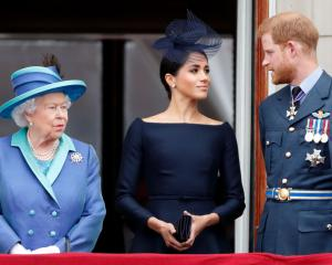 Queen Elizabeth II, Meghan, Duchess of Sussex and Prince Harry, Duke of Sussex watch a flypast to...