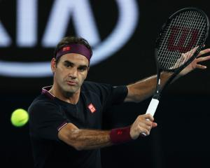 Roger Federer plays a backhand during his Australian Open match last night. Photo: Getty Images