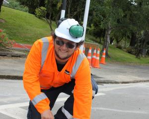 ITS electrician Hamish Watson screws an LED light into the road near the Kaikorai Valley College...
