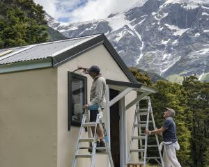 Graeme Stretch and Chris Milne apply their brushes to the Top Forks Hut beneath Mt Pollux, in the...