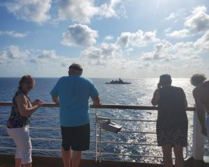 Passengers on board MS Westerdam watch Thai navy stealth frigate HTMS Bhumibol Adulyadej in...
