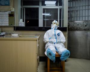 A medical worker takes a break during her night shift at a community health service centre in...