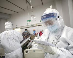 A medical worker in a protective suit checks a patient's records at Jinyintan hospital in Wuhan....