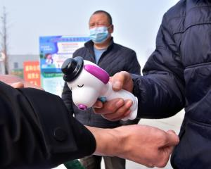 A guard measures the body temperature of a worker at the entrance to a factory in Shijiazhuang,...