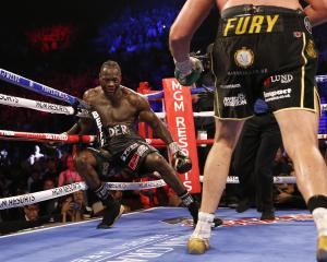 Tyson Fury knocks down Deontay Wilder during the fight. Photo: Reuters