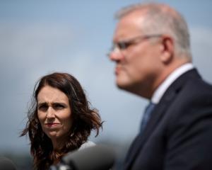 New Zealand Prime Minister Jacinda Ardern (L) and Australian Prime Minister Scott Morrison hold a...
