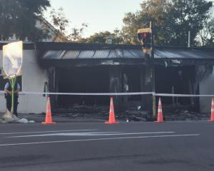 Police stand guard on Monday morning after a fire at Bristol Barbers on Wainoni Rd. Photo: Ian...