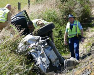 Police and fire personnel inspect a rolled vehicle on State Highway 1 near Lovells Flat, in South...