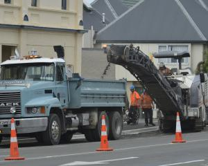 Fulton Hogan contractors use a milling machine to strip old asphalt from the surface of Great...