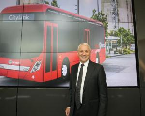 Mayor Phil Goff with an image of the electric bus. Photo: Auckland Transport