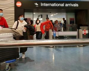 Passengers from international flights arrive at Auckland Airport wearing face masks in late...