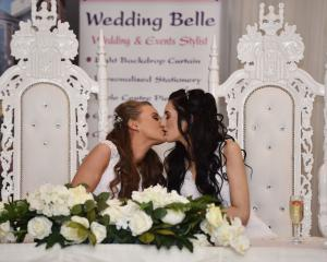 Robyn Peoples (L) and Sharni Edwards kiss after they became Northern Ireland's first legally...