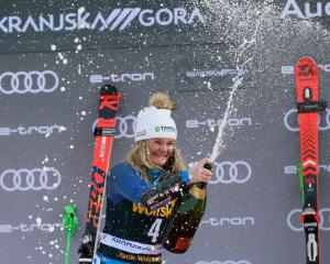 Alice Robinson celebrates her Women's Giant Slalom victory on the podium in Kranjska Gora,...