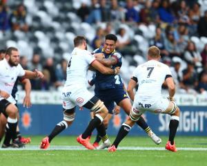Highlanders winger Tima Fainga'anuku takes the ball into contact as Sharks lock Ruben van Heerden...