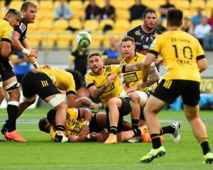 Hurricanes halfback TJ Perenara gets a pass away during the match against the Sharks. Photo:...