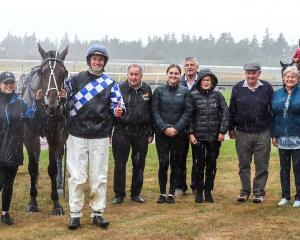 Trainer-driver Brad Williamson gives a thumbs up alongside the owners of Cracker Hill after the...