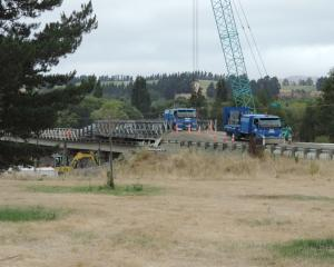 A truck travels over a Bailey bridge atop the Waiau River bridge, while earthquake repair work is...