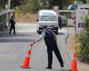 Police clear the way for Wuhan evacuees to leave the Whangaparaoa facility today. Photo: NZ Herald