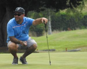 Mat Tautari, of Invercargill, gets ready to line up his putt on the 18th green on Sunday...