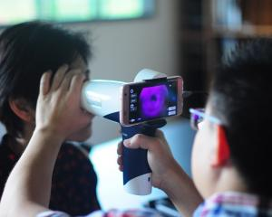 Dr Hong Sheng Chiong checks the retina of a farm worker at Batu Kawa, Kuching, in Sarawak. PHOTO:...