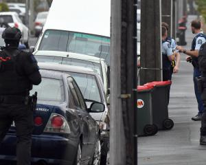 Armed police raid a Richmond St property in Forbury yesterday morning. Photo: Stephen Jaquiery
