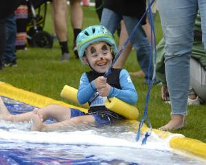 Elijah Mirkin (3), of Dunedin, zooms down the waterslide towards the finish line at the annual...