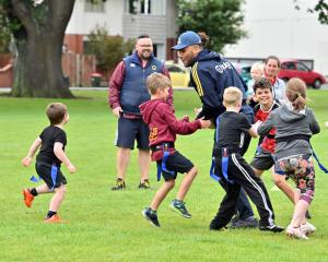 Highlanders loose forward Zane Kapeli tries to run past a bunch of children at the North Ground...
