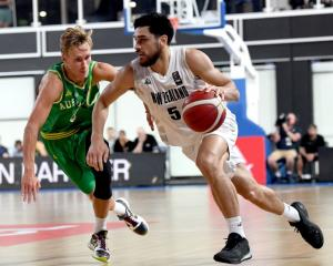 Tall Blacks guard Shea Ili drives past Boomers guard Kyle Adnam in Brisbane last night. Photo:...
