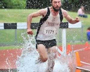 Caversham's Jonah Smith jumps into the water during the men's race at the Otago steeplechase...