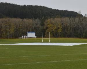 The pitch block at the University Oval was under cover yesterday. Wet weather has left the area...