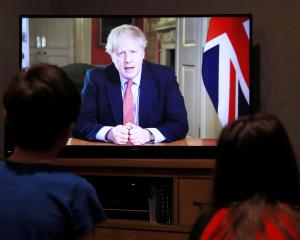 Children in the English town of Hertford watch British Prime Minister Boris Johnson's coronavirus...