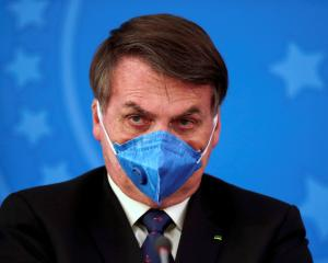 Brazil's President Jair Bolsonaro wears a protective face mask at a recent press conference in...
