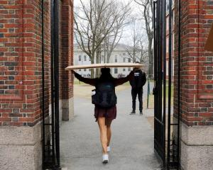 A student carries a box to her dormitory at Harvard University, after the university asked its...