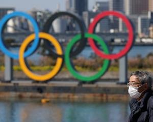 Man walks in front of the Giant Olympic rings at the waterfront area at Odaiba Marine Park in...