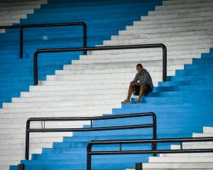 A ballboy waits in the empty stands of Presidente Peron Stadium before a Copa Libertadores...