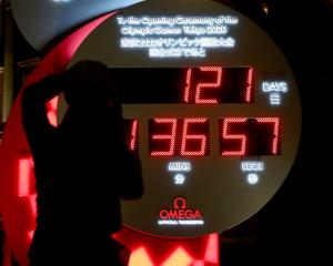 People in Tokyo watch the official Olympic countdown clock with the remaining days and time until...