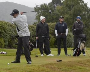 Howard Maxwell limbers up on the first tee at the Otago Golf Club on Saturday while looking on...