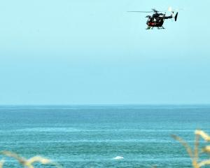 A rescue helicopter prepares to rescue a person from the water this afternoon. Photo: Christine O...