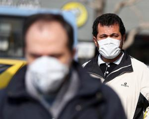 Men wear protective masks as they he walk on a street in Tehran, Iran. Photo: Reuters