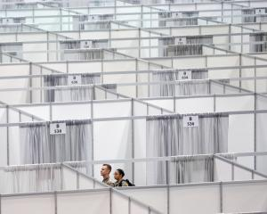 Military personnel walk among cubicles being prepared as part of phase 2 of the Javits New York...