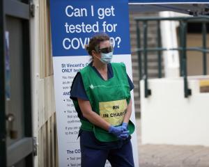 A healthcare professional waits at a pop-up clinic testing for coronavirus at Bondi Beach in...