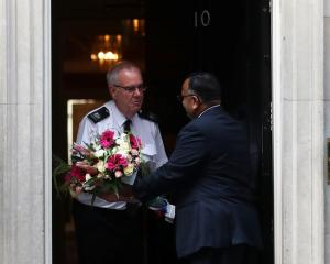 A man delivers flowers to 10 Downing Street. Photo: Reuters
