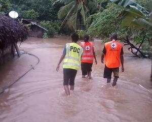 Volunteers walk through floodwaters in Vanuatu in the aftermath of Cyclone Harold. Photo: VANUATU...