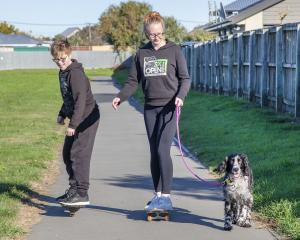 Skateboarding and exercising the dog at the Rawhiti School bike track, New Brighton.