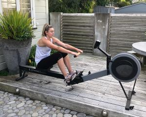 Gina Crampton on the rowing machine at her Wellington base. PHOTO SUPPLIED
