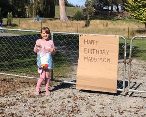 Madison Wall (7), of Balclutha, outside the property of a neighbour who made her a sign and set...
